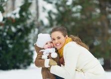 Porträt der glücklichen Mutter und Baby im Winter parken stockbilder