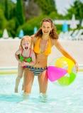 Porträt der glücklichen Mutter und des Babys im Pool lizenzfreie stockfotos