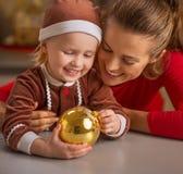 Porträt der glücklichen Mutter und des Babys mit Weihnachtsball Lizenzfreie Stockbilder