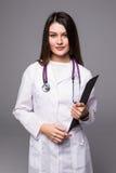 Porträt der glücklichen recht jungen Ärztin mit Klemmbrett und Stethoskop über weißem Hintergrund Lizenzfreie Stockbilder