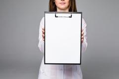 Porträt der glücklichen recht jungen Ärztin mit Klemmbrett und Stethoskop über weißem Hintergrund Stockbild