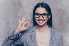 Porträt der glücklichen recht jungen Frau in den Gläsern steht auf grauem b stockbild