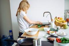 Porträt der glücklichen weiblichen Frau im weißen T-Shirt Abendessen an der Küche kochend Lizenzfreies Stockbild