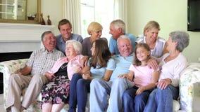Porträt der große Familien-Gruppe, die auf Sofa At Home sitzt stock footage