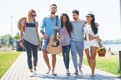 Porträt der Gruppe Freunde, die auf zum Strand gehen Gemischte Gruppe Freunde, die auf den Strand am Sommertag gehen Lizenzfreie Stockbilder