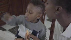 Porträt der hübschen Afroamerikanerfrau, die mit ihrem kleinen Sohn durch die Tabelle spielt zusammen mit Plätzchen sitzt familie stock video footage