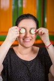 Porträt der hübschen Frau, die Spaß mit einer Gurke in der Küche hat Stockbilder
