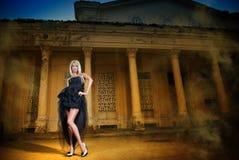 Porträt der hübschen Frau draußen stehend im schwarzen eleganten Kleid Lizenzfreie Stockfotografie