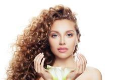 Porträt der hübschen Frau mit dem langen gelockten Haar, klarer Haut und Lilienblume in ihren Händen lokalisiert auf weißem Hinte stockbilder