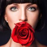 Porträt der hübschen Frau mit Rotrose im Mund stockfotografie