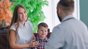 Porträt der hübschen jungen europäischen Mutter und des kleinen Sohns an der Aufnahme männlichen Doktors stock footage