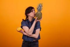 Porträt der hübschen jungen Frau, die eine Ananas küsst und eine frische Orange im Studio über gelbem Hintergrund hält lizenzfreies stockfoto