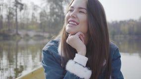 Porträt der hübschen jungen Frau, die im Boot auf dem Fluss, schauend um das Lächeln sitzt Verbindung mit Natur aktiv stock video footage