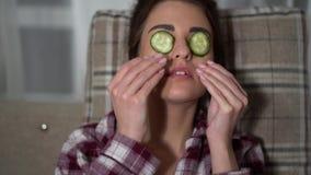 Porträt der hübschen jungen Frau Maske im von den Gurken am gemütlichen Abend machenden, kühlenden und entspannenden Pyjama Augen stock video footage