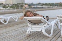 Porträt der hübschen jungen Kieme, welche die Kamera liegt auf Sonnenruhesessel betrachtet lizenzfreie stockbilder