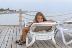 Porträt der hübschen jungen Kieme, welche die Kamera liegt auf Sonnenruhesessel betrachtet stockbild