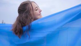 Porträt der hübschen Mädchenstellung auf einem Mohnblumengebiet umfasst mit Flagge von Ukraine Verbindung mit Natur, Patriotismus stock footage