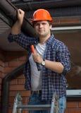 Porträt der hübschen männlichen Arbeitskraft im Schutzhelm, der Haus repariert lizenzfreie stockfotos