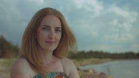 Porträt der hübschen Rothaarigefrau, die an der Küste lächelt stock video