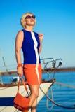Porträt der herrlichen blonden Frau von mittlerem Alter im modischen Kleid und in der Sonnenbrille, die eine orange Tasche hält u Stockfotografie