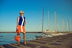 Porträt der herrlichen blonden Frau von mittlerem Alter im modischen Kleid und in der Sonnenbrille, die eine orange Tasche hält Stockbilder