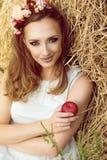 Porträt der herrlichen Frau in den weißen sundress, die am Heuschober mit der Girlande von Blumen auf ihrem Kopf, einen roten Apf Stockfoto