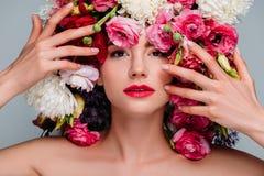 Porträt der herrlichen jungen Frau mit Blumen auf dem Kopf, der Kamera betrachtet stockfotografie
