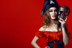 Porträt der herrlichen sexy Frau mit provozierendem Make-up im Piratenkostüm, das Schädelmaske nahe bei ihrem Gesicht hält lizenzfreies stockbild
