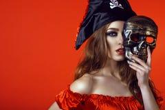Porträt der herrlichen sexy Frau mit provozierendem Make-up im Piratenkostüm, welches die Hälfte ihres Gesichtes hinter Schädelma Lizenzfreie Stockbilder
