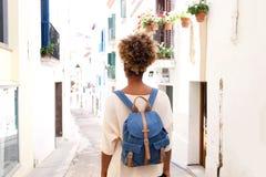 Porträt der hinteren Ansicht der Afroamerikanerfrau gehend auf Straße mit Tasche Stockbilder