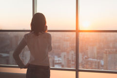 Porträt der hinteren Ansicht des jungen Arbeitnehmers sprechend unter Verwendung des Handys, das Fenster heraus schauend Weiblich Stockbilder
