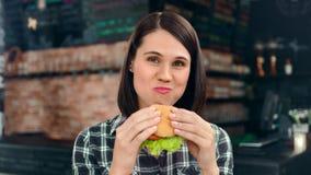 Porträt der hungrigen lächelnden Jugendfrau, die den Schnellimbiß betrachtet mittlere Nahaufnahme der Kamera isst stock video footage