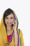 Porträt der indischen Frau in der traditionellen Abnutzung, die an Telefonanruf über weißem Hintergrund teilnimmt Stockbild