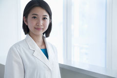 Porträt der jungen Ärztin im Krankenhaus, Kamera betrachtend lizenzfreie stockfotos