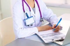 Porträt der jungen Ärztin im weißen Mantel am Computer Lizenzfreie Stockfotografie