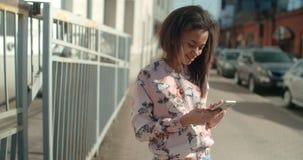 Porträt der jungen Afroamerikanerfrau, die Telefon, draußen verwendet Lizenzfreie Stockfotografie