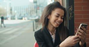 Porträt der jungen Afroamerikanerfrau, die Telefon, draußen verwendet Stockfotografie