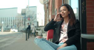 Porträt der jungen Afroamerikanerfrau, die Telefon, draußen verwendet Stockbilder