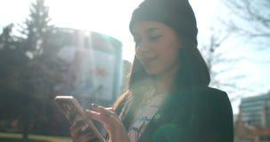 Porträt der jungen Afroamerikanerfrau, die Telefon, draußen verwendet Lizenzfreie Stockfotos