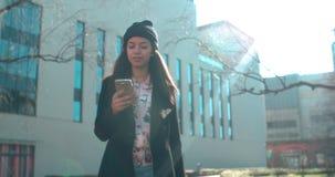 Porträt der jungen Afroamerikanerfrau, die Telefon, draußen verwendet Lizenzfreies Stockbild