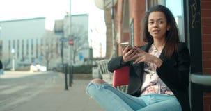 Porträt der jungen Afroamerikanerfrau, die Telefon, draußen verwendet Stockfoto