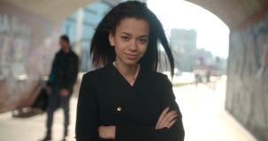 Porträt der jungen Afroamerikanerfrau, die zu einer Kamera, draußen schaut Stockfoto