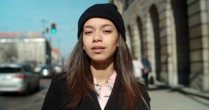 Porträt der jungen Afroamerikanerfrau, die zu einer Kamera, draußen schaut Stockbild