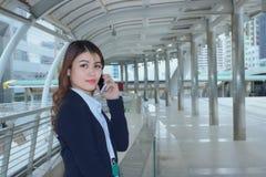 Porträt der jungen asiatischen Geschäftsfrau des hübschen Gesichtes, die am Telefon am städtischen Stadthintergrund spricht stockbild