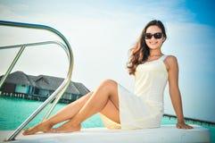 Porträt der jungen asiatischen schauenden Frau, die auf Boot am tropischen Strand bei Malediven sitzt Lizenzfreie Stockfotografie