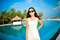 Porträt der jungen asiatischen schauenden Frau, die vor Swimmingpool am tropischen Strand bei Malediven steht Lizenzfreies Stockbild