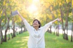 Porträt der jungen asiatischen steigenden Hand der Frau und des Buches in der Hand als VI Lizenzfreies Stockfoto