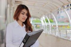 Porträt der jungen attraktiven asiatischen Geschäftsfrau, die Dokumentenordner an der Bahn des äußeren Büros mit Kopienraumhinter Lizenzfreie Stockbilder