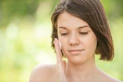 Porträt der jungen attraktiven Frau, die Creme auf ihr Gesicht setzt Lizenzfreie Stockbilder