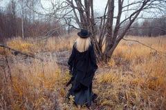 Porträt der jungen attraktiven Frau im schwarzen Mantel und im Hut Sie läuft das Feld durch Herbstlandschaft, trockenes Gras blic Lizenzfreie Stockfotografie